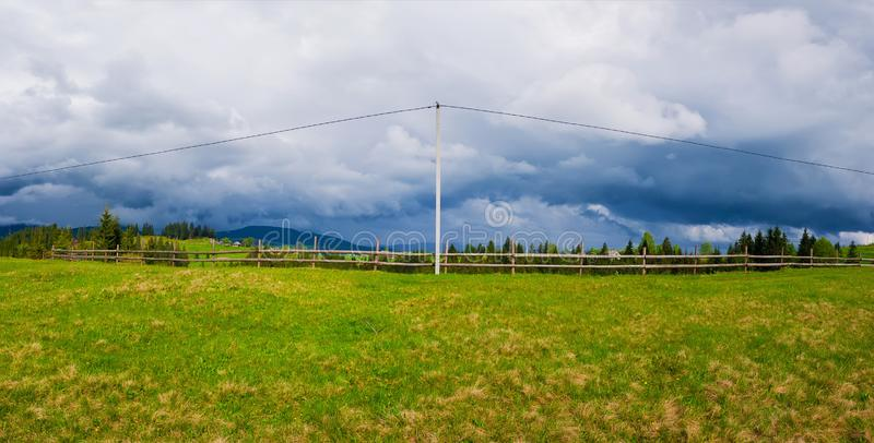 Electric power transmission pole in the mountains with cables along a wooden rail fence leading to the village. Panoramic royalty free stock image