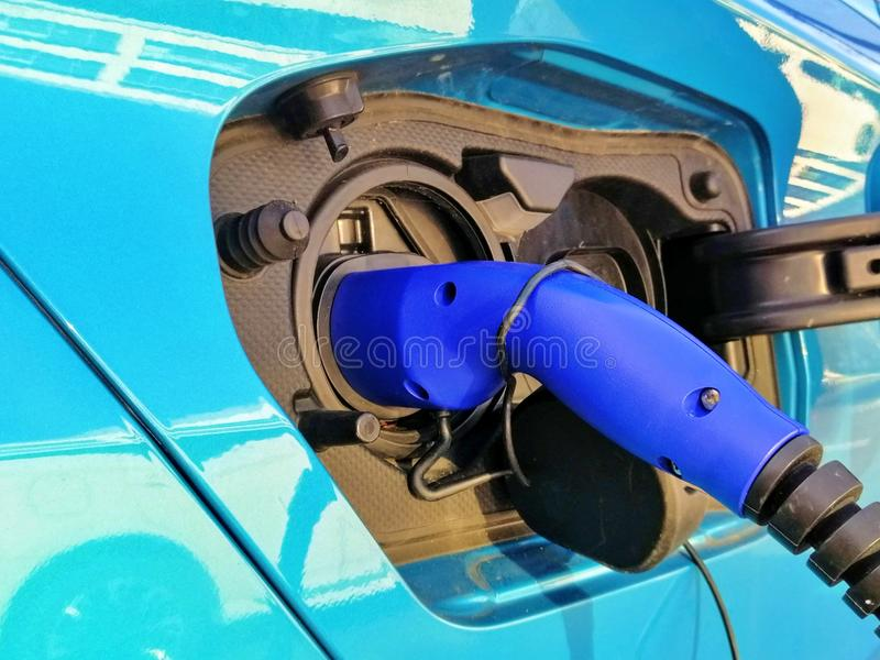 An electric powered car is being charged. Photo shows the charger inserted into the vehicles charging point royalty free stock photos