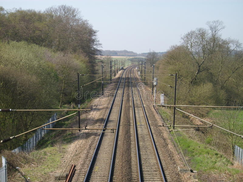 Electric railway line disappearing into the distance. And turning to the right. Two tracks. Overhead wires clearly visible with trees either side of the track stock images