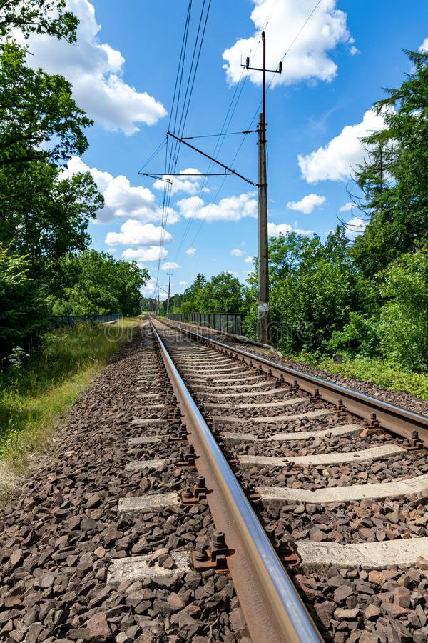 Electric railway traction in Central Europe. A railway line leading through a wooded area. Season of the summer, background, blue, business, cargo, crossing royalty free stock image