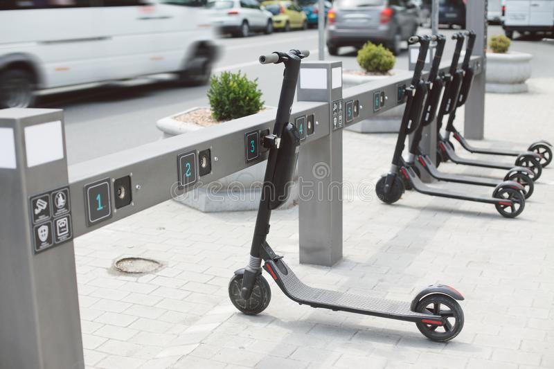 Electric schooters parked on the sidewalk avaliable for rent on the city street. Urban life concept. Eco-friendly transportation stock images