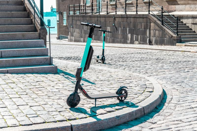 Electric scooter parked on the waterfront of the city. Zero emission green eco energy. Electric scooter parked on the waterfront of the city. Caring for the royalty free stock photography
