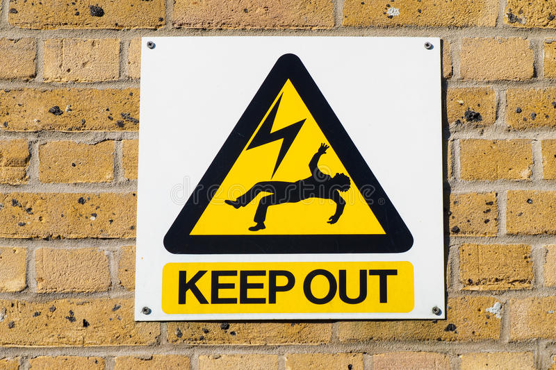 Electric shock death warning yellow sign on wall. Industrial warning plate in an electricity plant, signaling death danger for high voltage power in the royalty free stock images