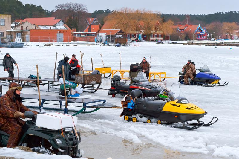 Electric sledge for delivery of fishermen on ice, snowmobiles for winter fishing stock images