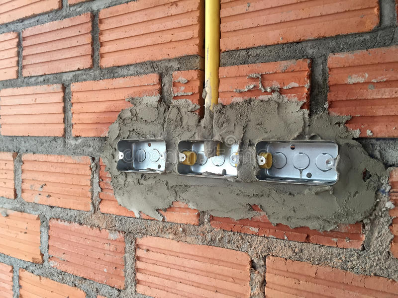 Electric sockets installation in brick walls at house construction site royalty free stock images