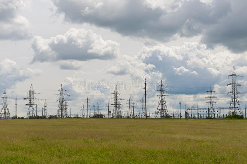 Electric substation in a green field in cloudy weather. Electric substation on the horizon in a green field in cloudy weather stock image