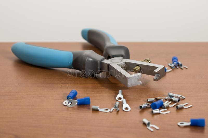 Electric tool, blue wire stripper on a wood table stock photo