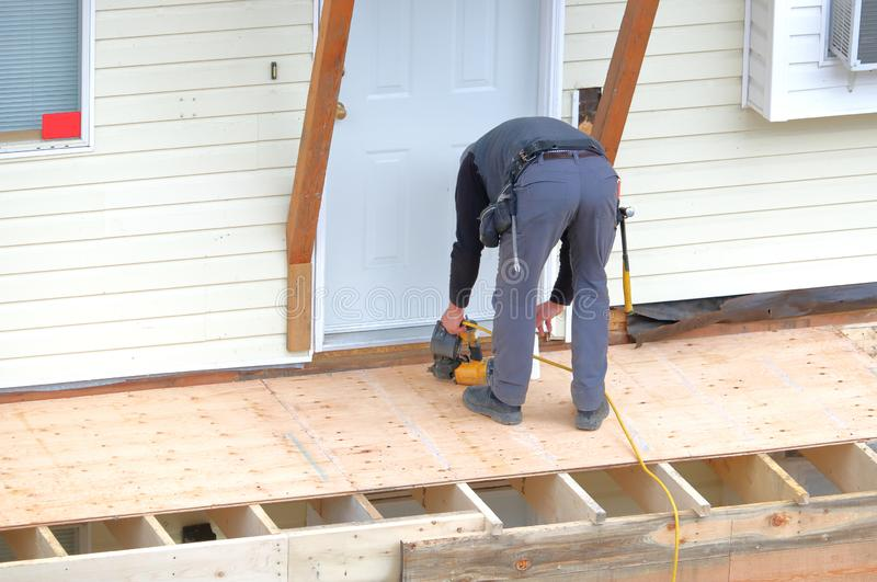 Electric Tools and Carpenter. A carpenter working outside on home renovations uses an electric nail gun to fasten plywood to a deck royalty free stock photo