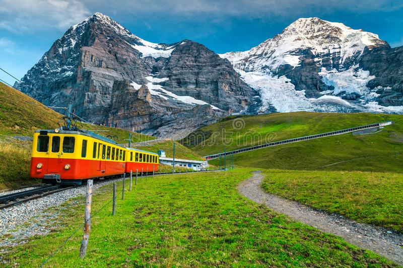 Electric tourist train and snowy Eiger mountain, Bernese Oberland, Switzerland stock photo