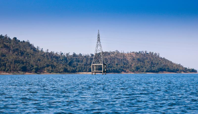 Electric tower on the lake, Silvassa, India royalty free stock images
