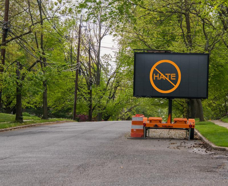 Electric traffic street sign on quiet neighborhood street that has a no hate symbol. Electric traffic street sign on quiet neighborhood street that has a no royalty free stock image