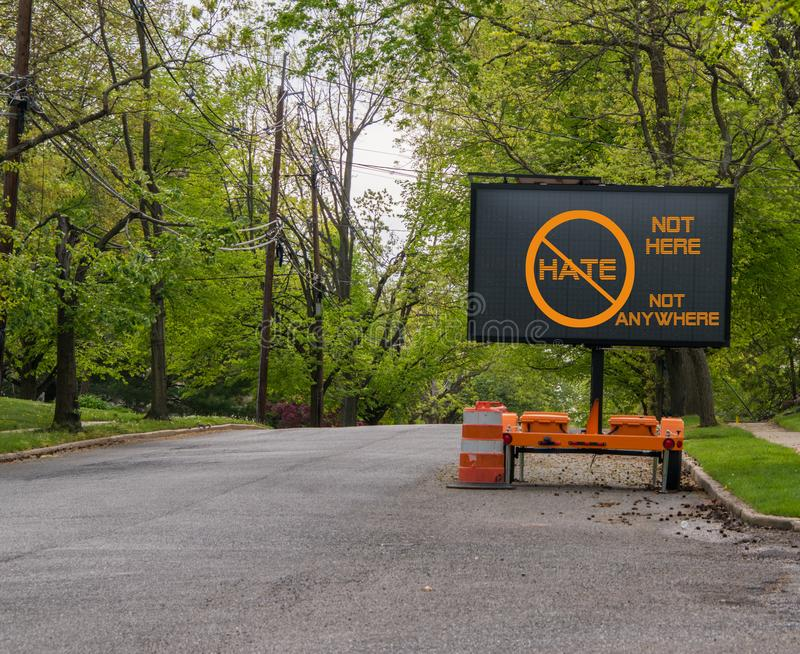 Electric traffic street sign on quiet neighborhood street that says no hate, not here, not anywhere. Electric traffic street sign on quiet neighborhood street royalty free stock image