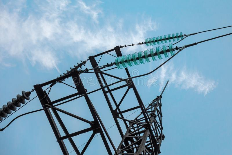 Electric transmission line tower with insulators and conductors. Closeup view on blue sky background. Concept of electric power stock image