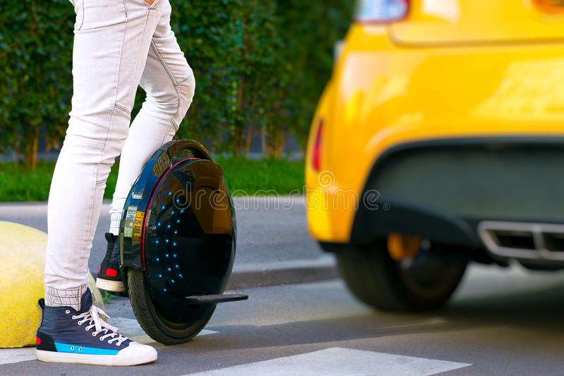 Electric transport compare to diesel fuel cars. Electric balancing unicycle. Future is now concept. Ecological transport. Black modern futuristic electric royalty free stock photo