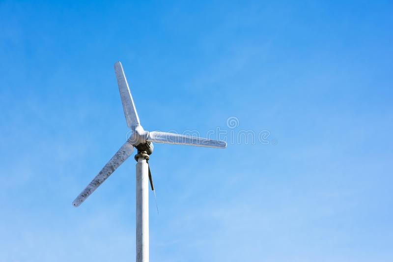 Electric wind turbine with blue sky background stock photography