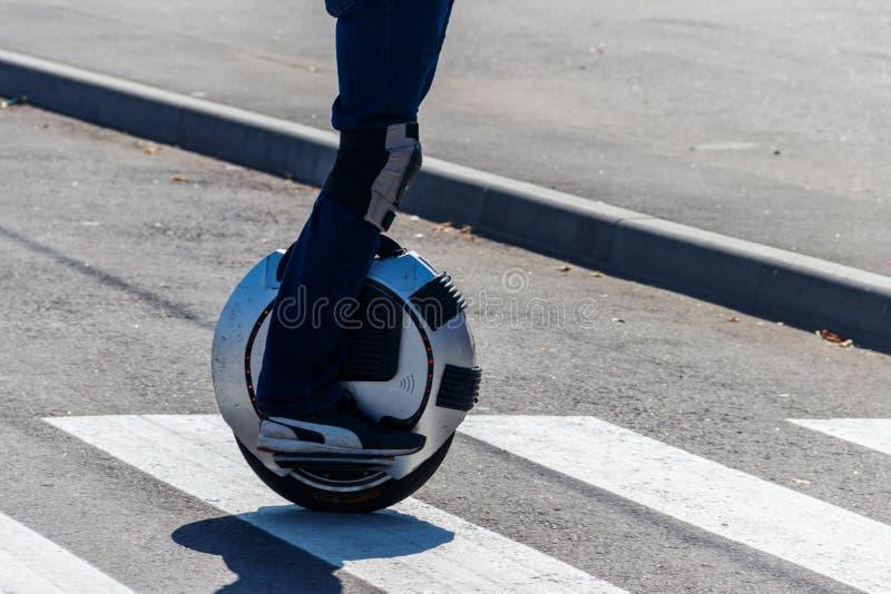 Electric unicycle. Man rides on mono wheel on zebra crossing stock photos