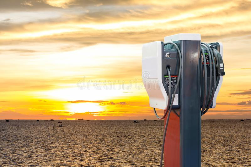 Electric vehicle charging Ev station with plug of power cable supply for Ev car on sea and sunrise background stock photography