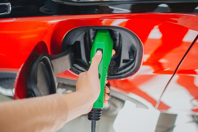 Electric vehicle charging station. Close-up of woman hand charging an electric car with the power cable supply plugged royalty free stock photography
