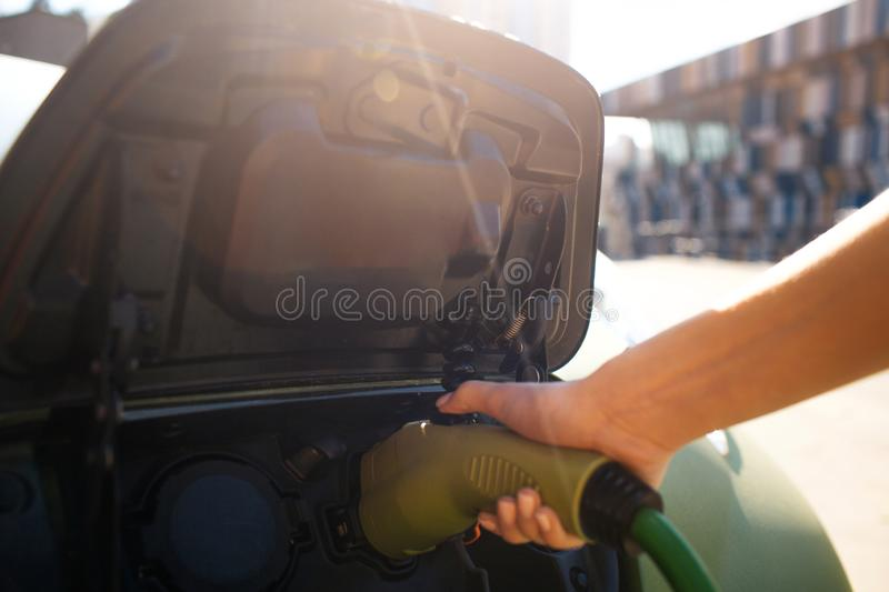 Electric vehicle charging station. Male hand charging an electric car with the power cable supply plugged in. Eco stock photos