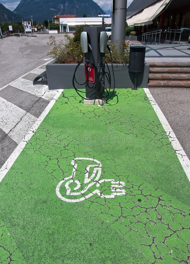 Electric Vehicle EV Charging Station parking spot with icon  text on aging green painted pavement royalty free stock photo