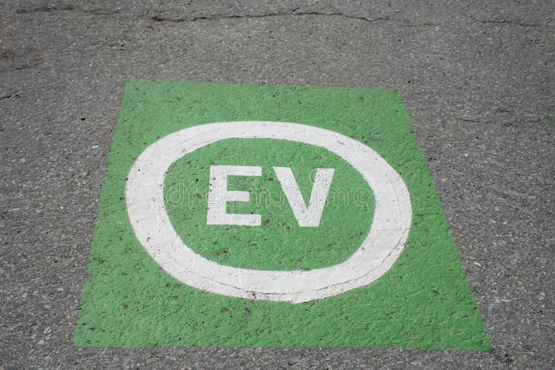 Electric vehicle green parking place for e-cars saving the environment from fuel and gas use.  royalty free stock photos