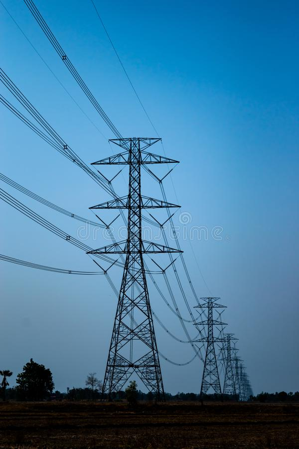 Electric voltage poles and electric cables, danger zone over dry fields in countryside landscape of Thailand. Electric voltage poles over dry fields in stock image
