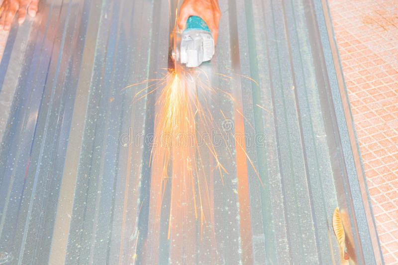 Electric wheel grinding on cutting metal sheet roof in constructor works. select focus with shallow depth of field.  royalty free stock photos