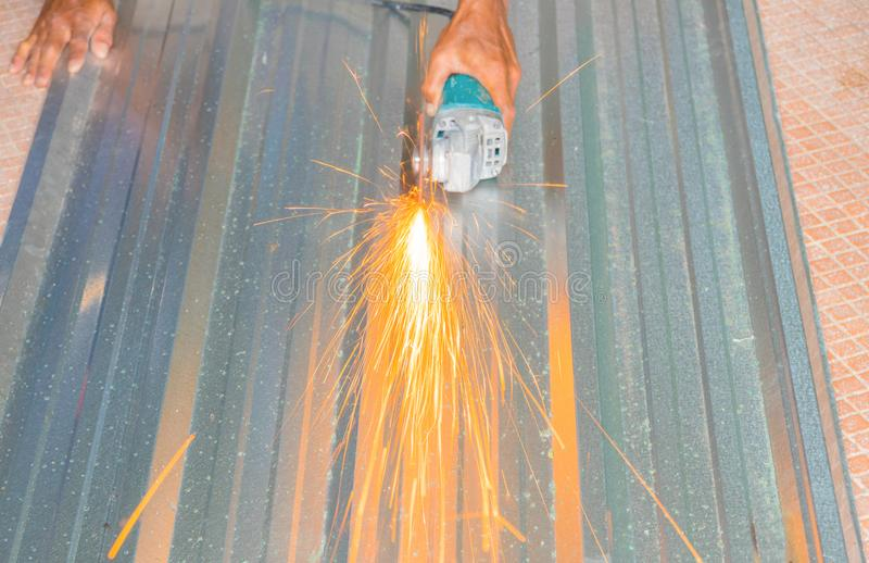 Electric wheel grinding on cutting metal sheet roof in constructor works. select focus with shallow depth of field.  stock photography