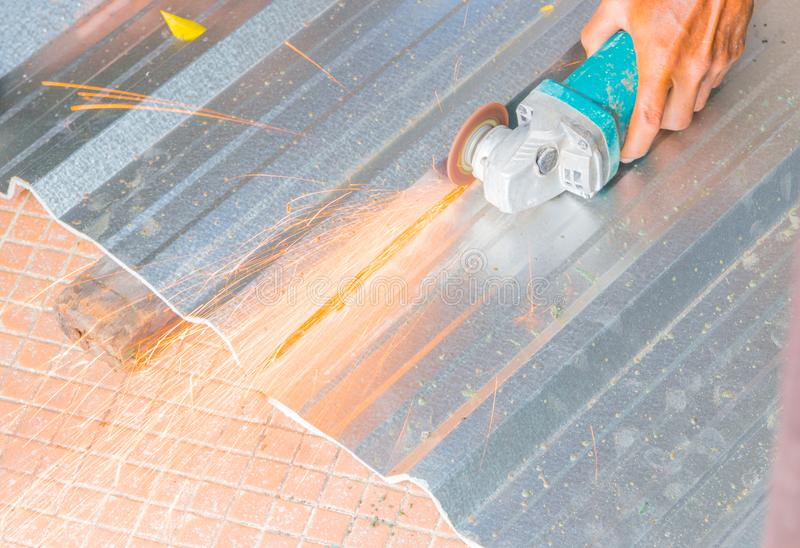 Electric wheel grinding on cutting metal sheet roof in constructor works. select focus with shallow depth of field.  stock images