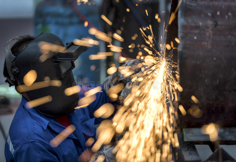 Electric wheel grinding on steel pipe. In factory stock photography