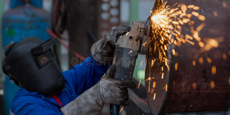 Electric wheel grinding on steel pipe in factory. (Focus on Tool stock image
