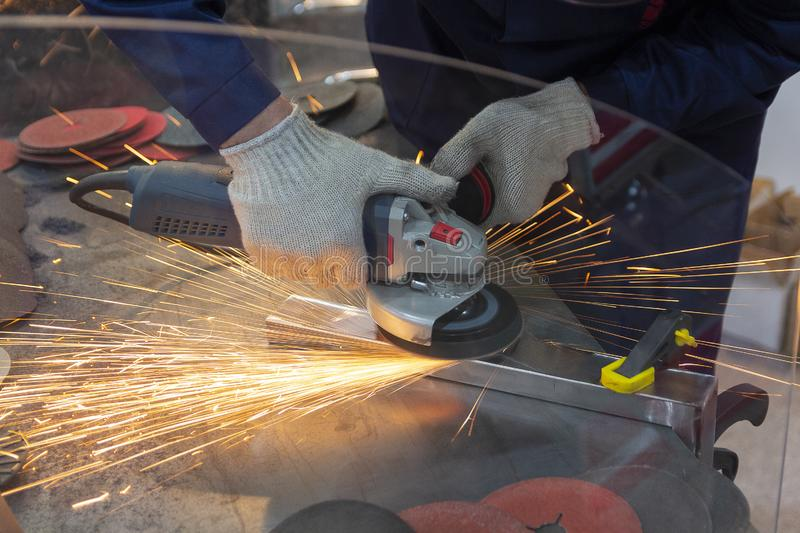 Electric wheel grinding on steel structure in factory stock image
