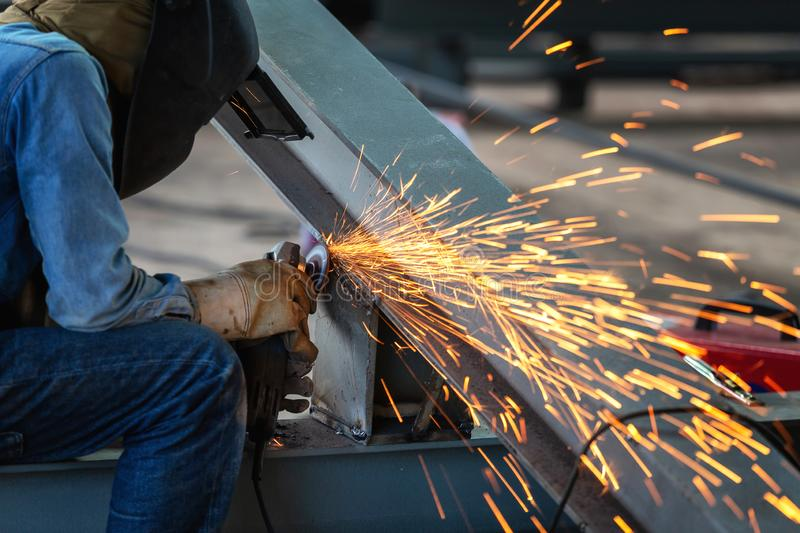 Electric wheel grinding on steel structure and welders with multiple sparks in factory. royalty free stock photo
