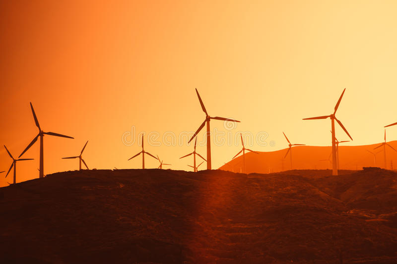 Electric wind turbines farm. Silhouettes on sunny background royalty free stock photography