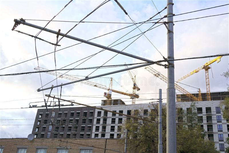 Electric wires and construction cranes in the modern city landscape royalty free stock image