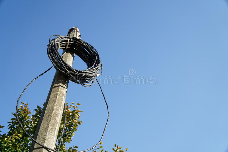 Electric wires rolled on post, bind cable stock images