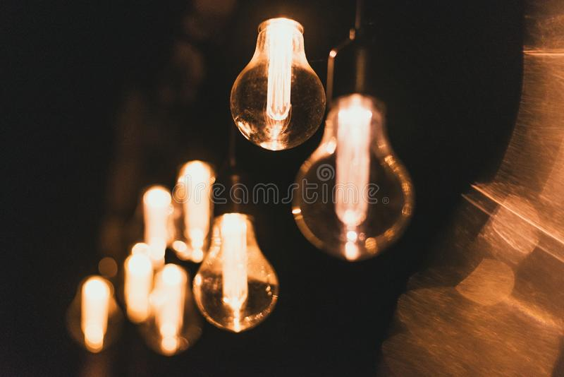 Electric yellow light bulbs on the street at night. Bulbs on the garland outsidoor royalty free stock photography