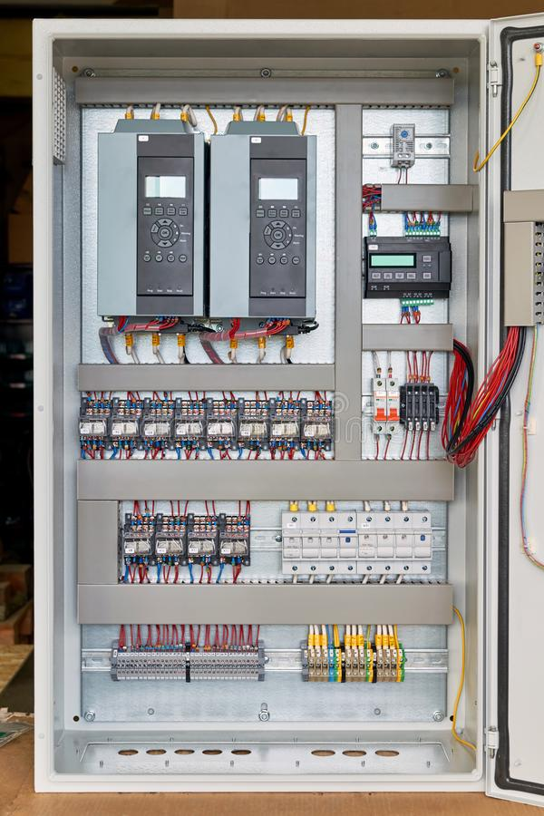 Electrical Cabinet with frequency converters, controller, circuit breaker. On the mounting panel mounted thermostat, intermediate relays and fuse holders. The royalty free stock photo