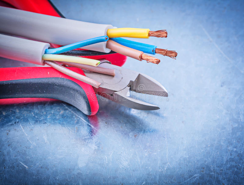 Electrical cables wires cutting pliers on metallic background co royalty free stock images