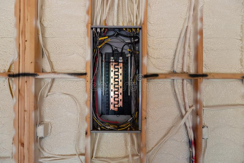 Electrical Circuit Breaker panel in new home construction, with spray foam insulation and negative space royalty free stock images
