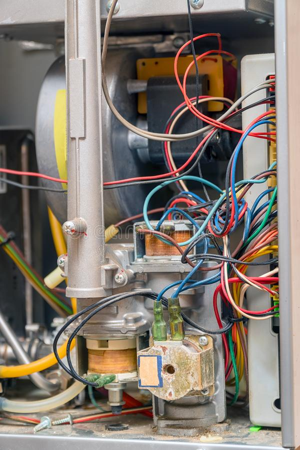 Electrical device with wires. Gas water heater inside. Repair gas water heater. Electrical device with wires. The gas water heater inside. Repair gas water stock photography