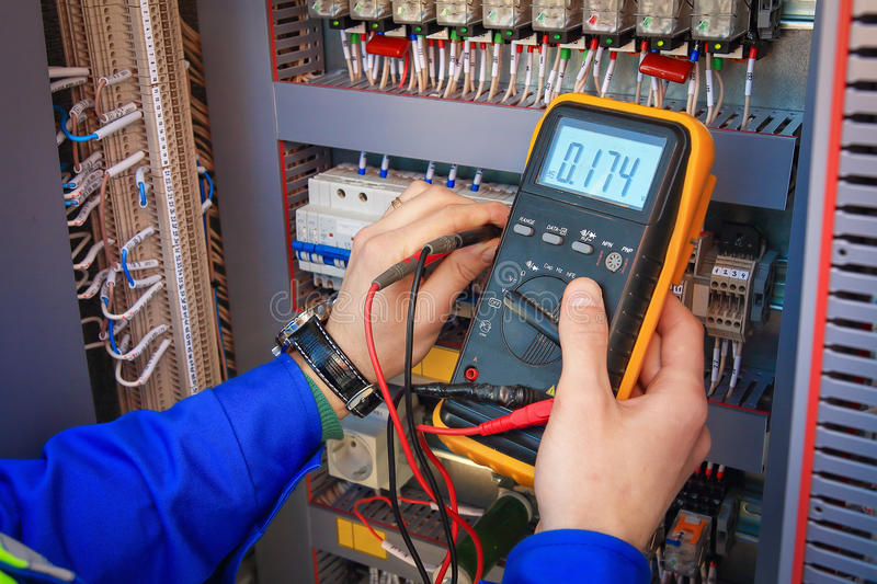 Electrical Engineer adjusts electrical equipment with a multimeter in his hand closeup. royalty free stock photos