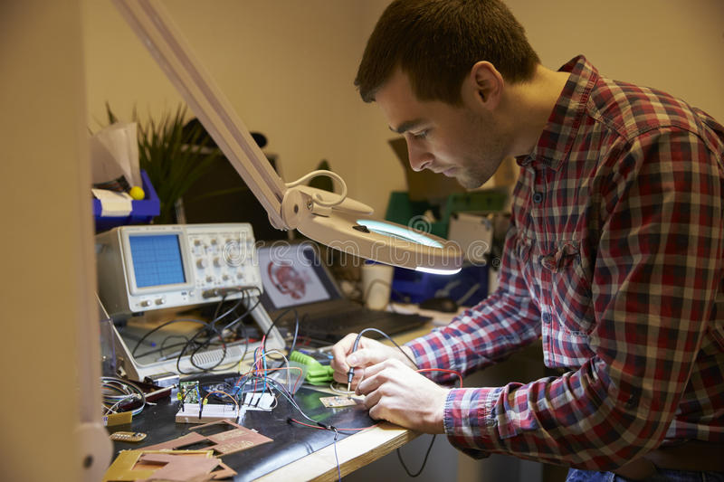 Electrical Engineer Soldering Circuit Board At Work Bench stock image