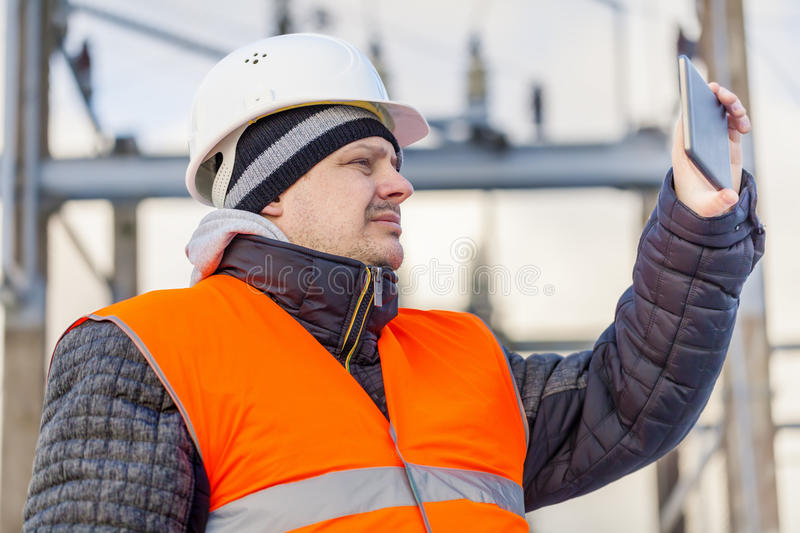 Electrical Engineer with tablet PC n electrical substation stock image