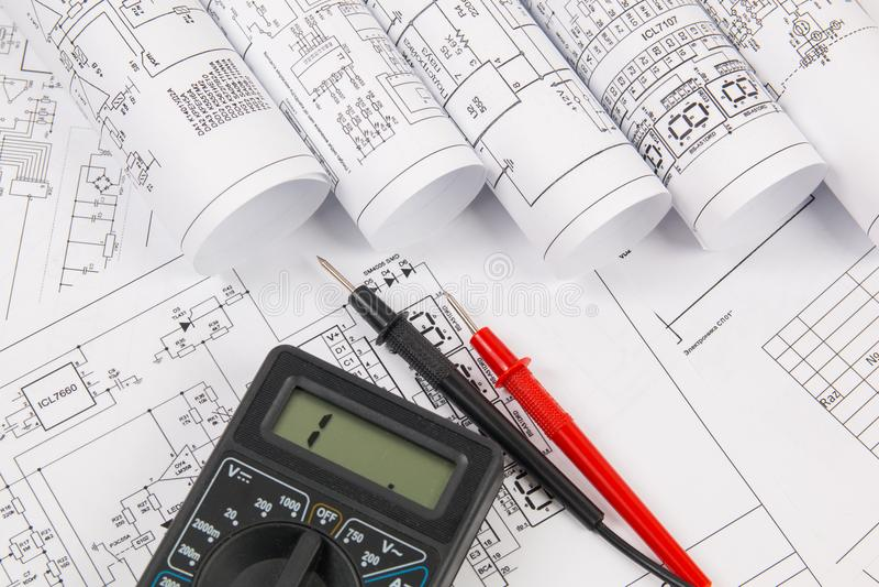 Electrical engineering drawings and digital multimeter royalty free stock photo