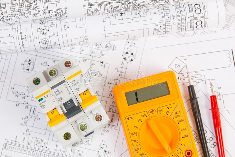 Electrical engineering drawings, modular circuit breaker and digital multimeter. Electrical network protection and switching royalty free stock photos
