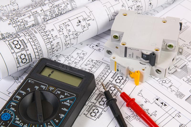 Electrical engineering drawings, modular circuit breaker and digital multimeter. Electrical network protection and switching royalty free stock photography