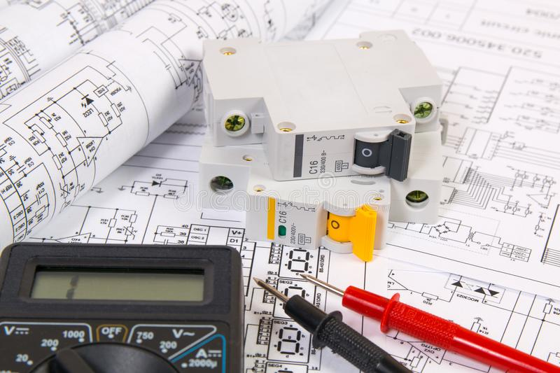 Electrical engineering drawings, modular circuit breaker and digital multimeter. Electrical network protection and switching stock images