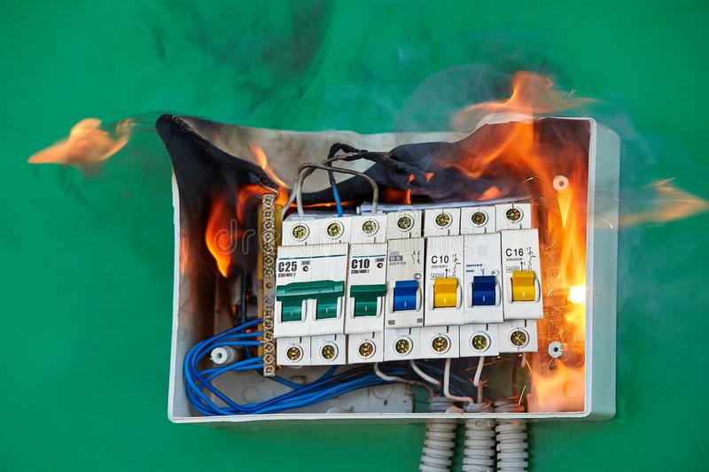 Bad electrical wiring caused fire in fuse box. Electrical faults of circuit breakers become the cause of fire. Loose wires caused fire inside electrical fuse box stock images