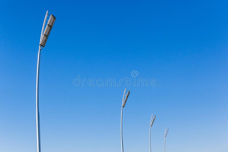 Electrical Floodlights Spotlights Towers Blue Sky. Four New electrical floodlight spotlights towers with powerful lights for night events over sports field in royalty free stock photos